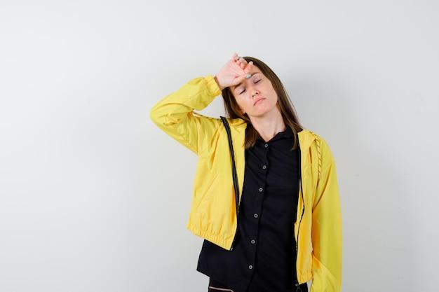 Młoda kobieta trzyma rękę na czole i wygląda na wyczerpaną