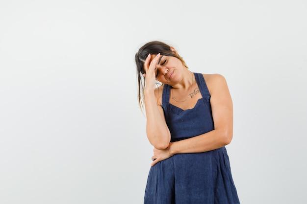 Młoda kobieta trzyma rękę na czole w ciemnoniebieskiej sukience i wygląda na zmęczoną