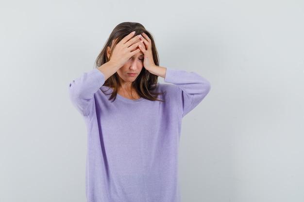 Młoda kobieta trzyma rękę na czole w liliowej bluzce i patrzy splątane