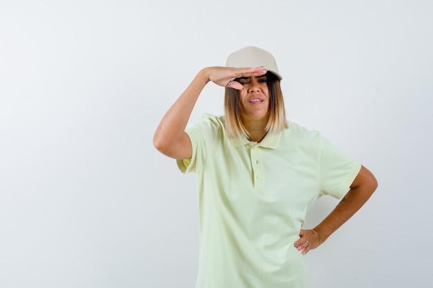 Młoda kobieta trzyma rękę na głowie, aby wyraźnie widzieć, trzymając rękę na talii w t-shirt, czapkę i patrząc skupiony, widok z przodu.