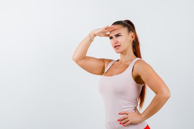 Młoda kobieta trzyma rękę na głowie, aby wyraźnie widzieć w białym podkoszulku i patrząc skupiony, widok z przodu.
