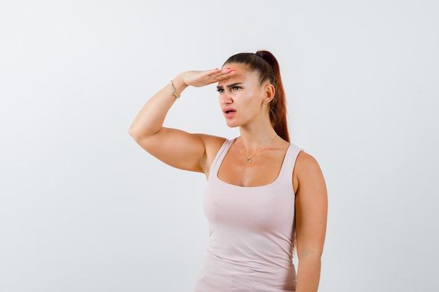 Młoda kobieta trzyma rękę na głowie, aby wyraźnie widzieć w podkoszulku i wyglądała na zdumioną. przedni widok.
