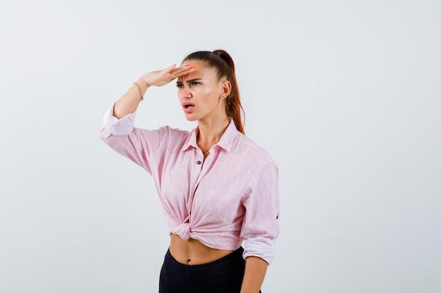 Młoda kobieta trzyma rękę na głowie, aby wyraźnie widzieć w zwykłej koszuli i wyglądająca zdziwiona, widok z przodu.