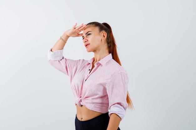 Młoda kobieta trzyma rękę na głowie, aby wyraźnie zobaczyć w zwykłej koszuli, spodniach i wyglądać pewnie
