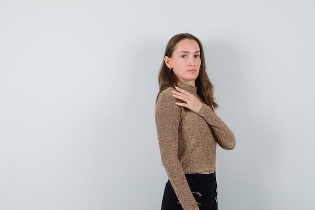 Młoda kobieta trzyma rękę na piersi i pozuje z przodu w pozłacanym swetrze i czarnych spodniach i wygląda uroczo