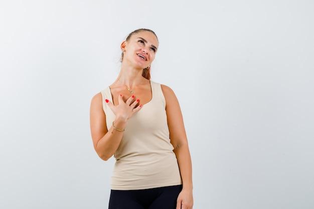 Młoda kobieta trzyma rękę na piersi w beżowym podkoszulku bez rękawów i wygląda na szczęśliwą