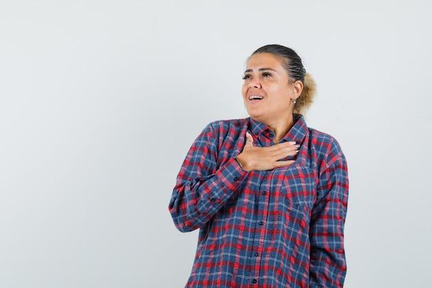 Młoda kobieta trzyma rękę na piersi w kraciastej koszuli i wygląda pod wrażeniem. przedni widok.