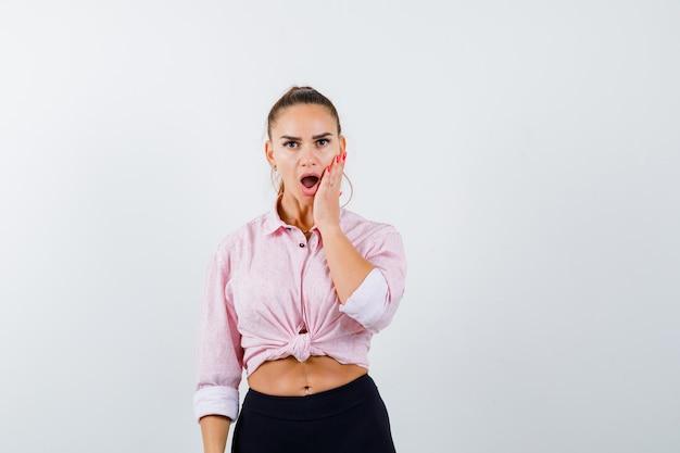 Młoda kobieta trzyma rękę na policzku w zwykłej koszuli i patrząc zdziwiony, widok z przodu.