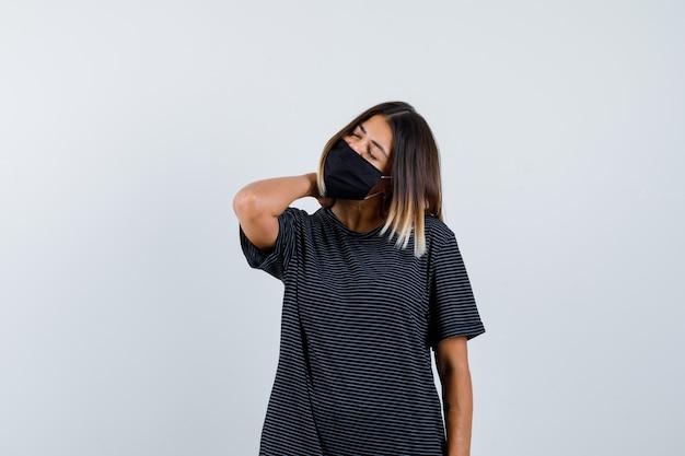 Młoda kobieta trzyma rękę na szyi, ma ból szyi w czarnej sukience, czarnej masce i wygląda na wyczerpaną, widok z przodu.