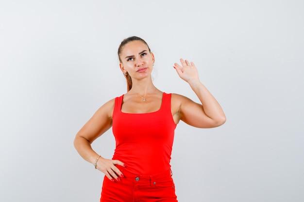 Młoda kobieta trzyma rękę na talii, pokazując gest stop w czerwonym podkoszulku, spodniach i patrząc pewnie, widok z przodu.