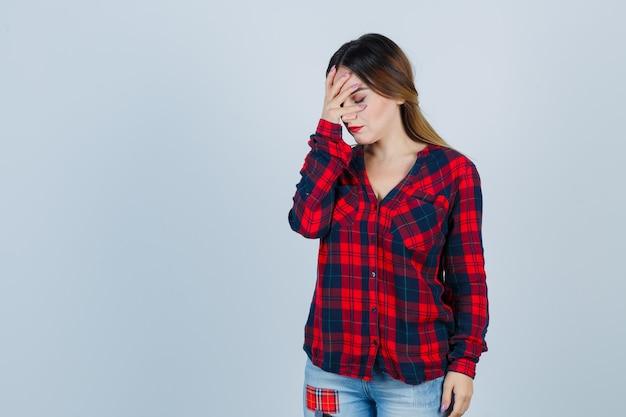 Młoda kobieta trzyma rękę na twarzy w kraciastej koszuli i wygląda na zmęczoną, widok z przodu.