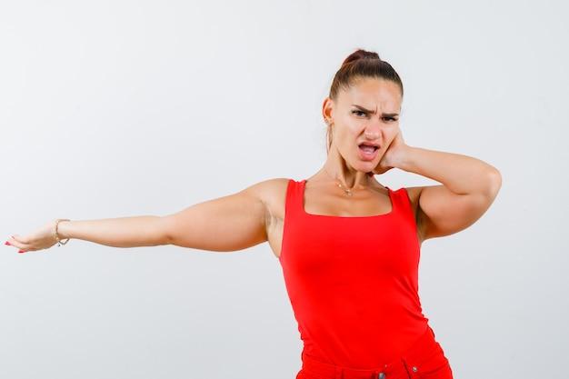 Młoda kobieta trzyma rękę na uchu podczas rozciągania ramienia w czerwonym podkoszulku, spodniach i wygląda na zaniepokojoną. przedni widok.