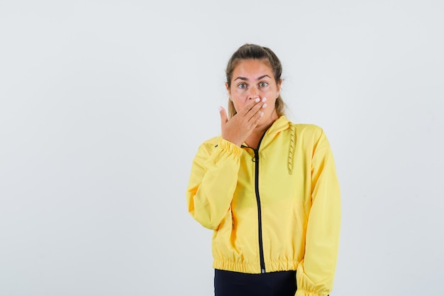 Młoda kobieta trzyma rękę na ustach w żółtym płaszczu przeciwdeszczowym i wygląda na zaskoczonego