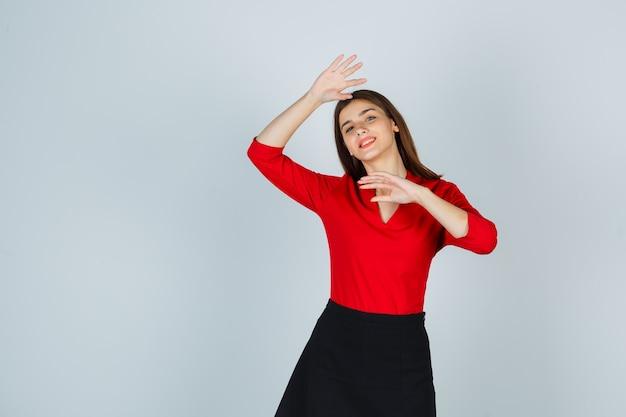 Młoda kobieta trzyma rękę pod brodą, macha ręką na powitanie w czerwonej bluzce