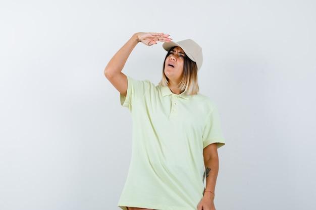 Młoda kobieta trzyma rękę w pobliżu czapki, aby wyraźnie zobaczyć w t-shirt, czapkę i patrząc skoncentrowany, widok z przodu.