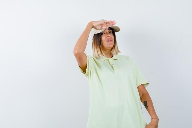 Młoda kobieta trzyma rękę w pobliżu czapki, aby wyraźnie zobaczyć w t-shirt, czapkę i wyglądający pewnie. przedni widok.