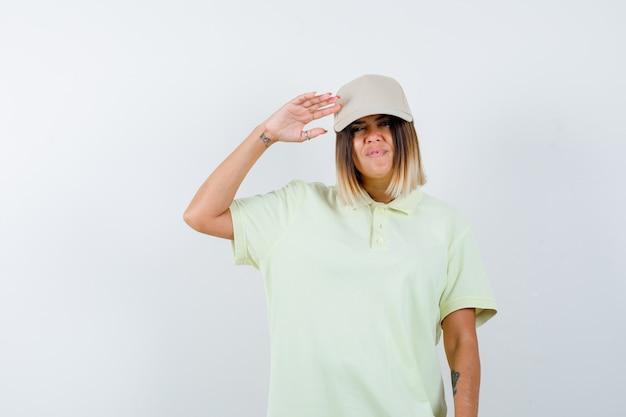 Młoda kobieta trzyma rękę w pobliżu głowy za salutowanie w t-shirt, czapkę i wyglądający pewnie. przedni widok.