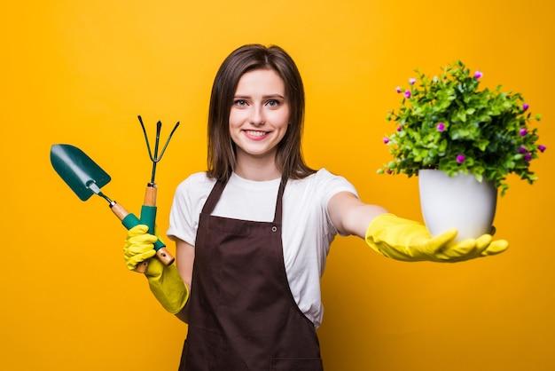 Młoda kobieta trzyma roślinę i narzędzia na białym tle
