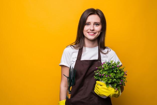 Młoda kobieta trzyma roślinę na białym tle