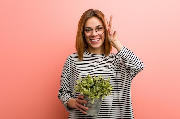 Młoda kobieta trzyma rośliny pokazuje zwycięstwo znaka i uśmiecha się szeroko.