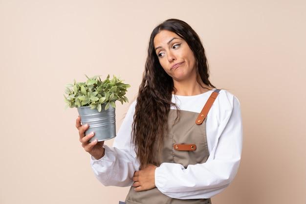 Młoda kobieta trzyma rośliny z smutnym wyrażeniem