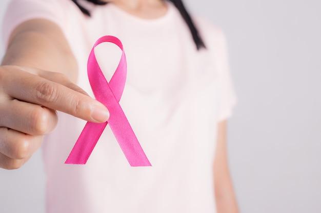 Młoda kobieta trzyma różową wstążkę. miesiąc świadomości raka piersi.