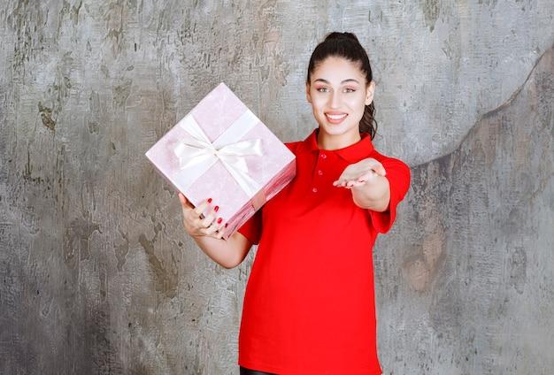 Młoda kobieta trzyma różowe pudełko owinięte białą wstążką i dzwoniąc do osoby z przodu, aby je przedstawić.