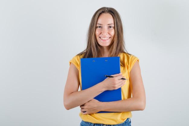 Młoda kobieta trzyma schowek i długopis w t-shirt, spodenki i wesoły wyglądający