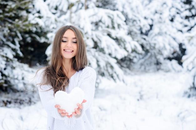 Młoda kobieta trzyma serce od śniegu w zima lesie.