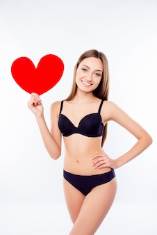 Młoda kobieta trzyma serce w czarnej bieliźnie