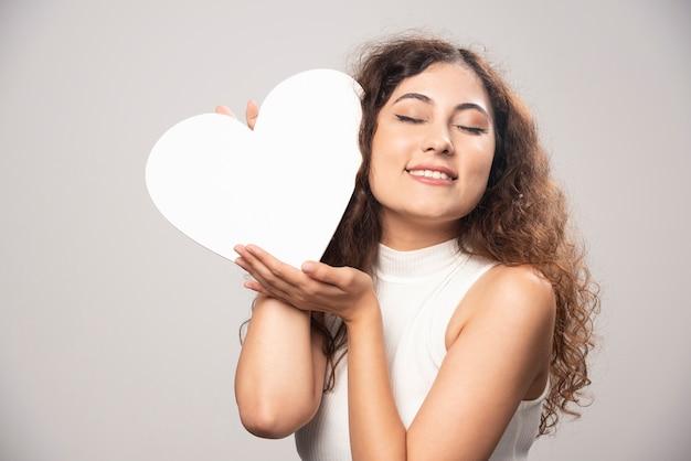 Młoda kobieta trzyma serce z białego papieru czerpanego. wysokiej jakości zdjęcie