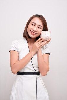 Młoda kobieta trzyma skarbonkę na białym tle