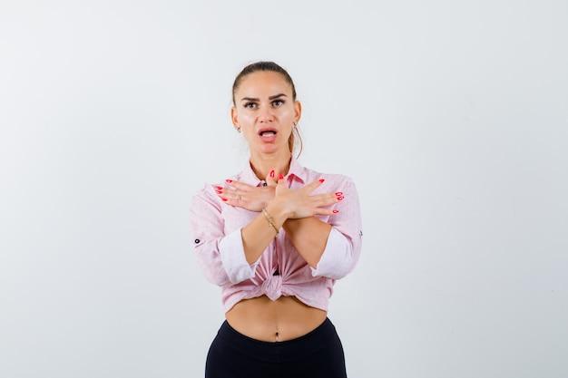 Młoda kobieta trzyma skrzyżowane ręce na piersi w zwykłej koszuli, spodniach i wygląda zdziwiona. przedni widok.