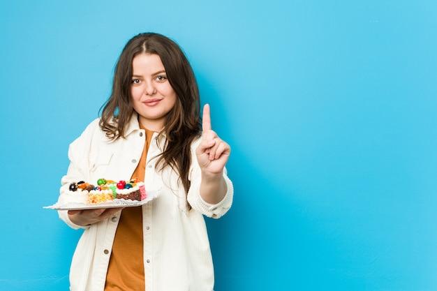 Młoda kobieta trzyma słodkich torty pokazuje liczbę jeden z palcem.