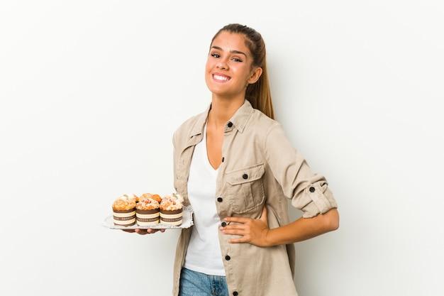 Młoda kobieta trzyma słodkie ciasta, śmiejąc się i zabawy