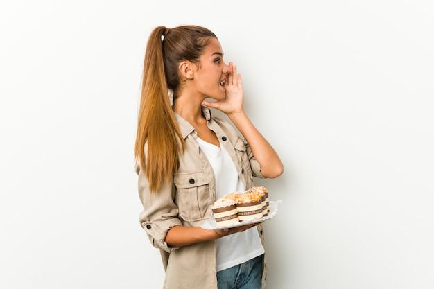 Młoda kobieta trzyma słodkie ciasta