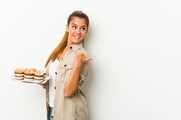 Młoda kobieta trzyma słodkie ciastka punktów z kciukiem palcem, śmiejąc się i beztroski