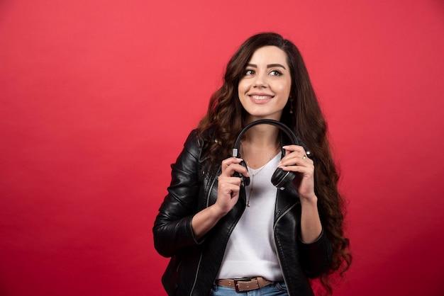 Młoda kobieta trzyma słuchawki i pozowanie na czerwonym tle. zdjęcie wysokiej jakości