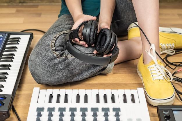 Młoda kobieta trzyma słuchawki studyjne. kobieta muzyk siedzi w domowym studio z nowoczesnymi instrumentami elektronicznymi.