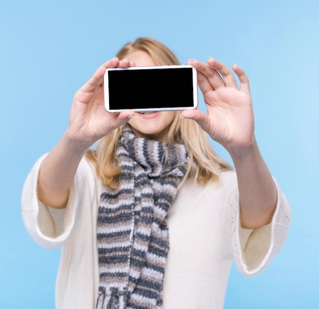 Młoda kobieta trzyma smartphone