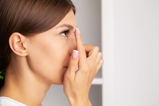 Młoda kobieta trzyma soczewki kontaktowe na palcu.