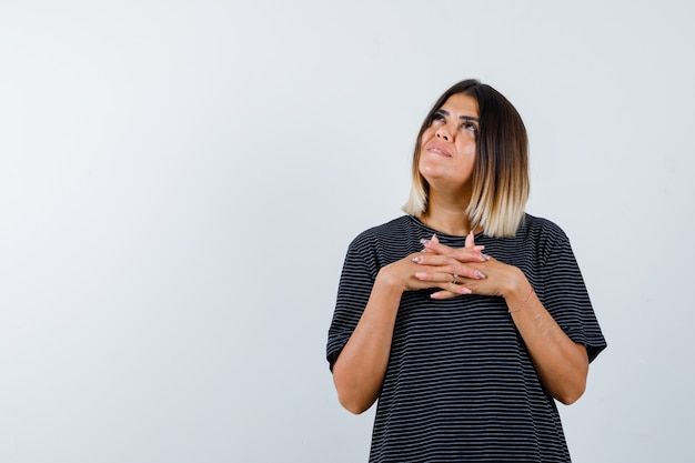 Młoda kobieta trzyma splecione ręce na piersi, odwracając wzrok w czarnej sukni i ładnie wyglądający widok z przodu.