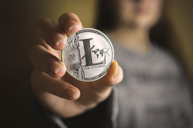 Młoda kobieta trzyma srebrny litecoin w dłoni zbliżenie, reklama monet kryptograficznych, koncepcja waluty cyfrowej zdjęcie tła biznesowego