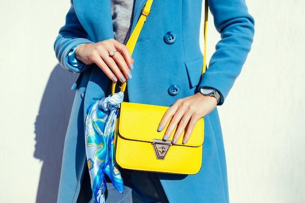 Młoda kobieta trzyma stylową żółtą torebkę i modny niebieski płaszcz. wiosenne ubrania i akcesoria dla kobiet. moda. kolor 2021
