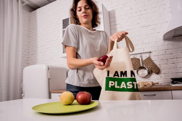 Młoda kobieta trzyma sukienną torbę. w kuchni nie jestem plastykiem. kampania na rzecz ograniczenia użycia plastikowych toreb. zero marnowania