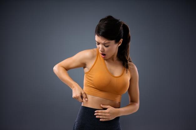 Młoda kobieta trzyma swój tłusty brzuch i jest dość nieprzyjemnie zaskoczona.