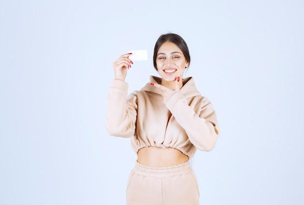 Młoda kobieta trzyma swoją wizytówkę i przedstawia