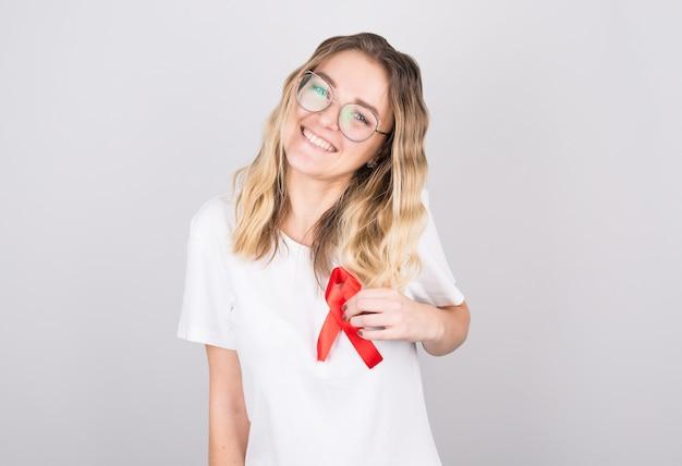 Młoda kobieta trzyma symbol świadomości czerwoną złotą wstążką dla endometriozy, zapobiegania samobójstwom, mięsaka raka kości, raka pęcherza, raka wątroby i koncepcji raka u dzieci.