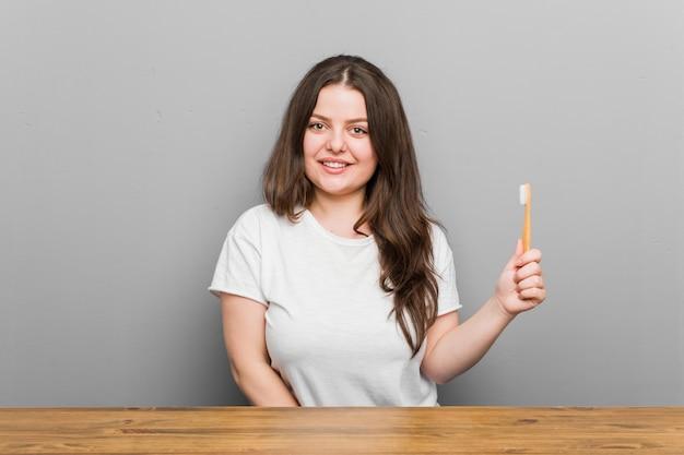 Młoda kobieta trzyma szczoteczkę do zębów szczęśliwa, uśmiechnięta i wesoła.