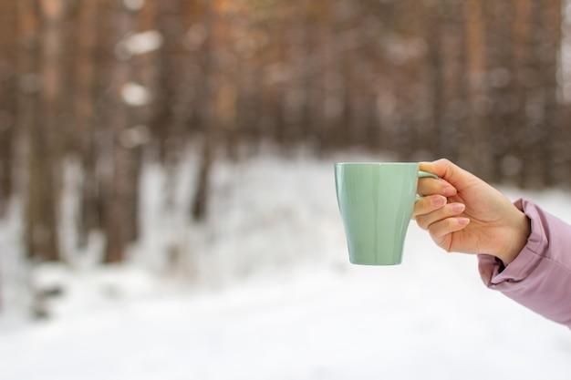 Młoda kobieta trzyma szklankę gorącej kawy lub herbaty w lesie zimą. śnieżna zima i gorący napój do ogrzania. kubek gorącej kawy lub herbaty